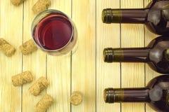 Bicchiere di vino su fondo delle bottiglie e dei sugheri Immagini Stock