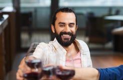 Bicchiere di vino tintinnante dell'uomo felice al ristorante fotografia stock libera da diritti