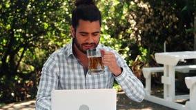 Bicchiere sorridente dell'uomo di birra mentre lavorando al computer portatile video d archivio