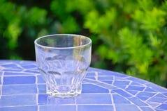 Bicchiere sulla tavola blu Fotografie Stock