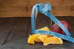Bicchieri d'acqua e frutta Alimento per perdita di peso Apple sopra il taccuino Dieta controllata Dieta sana per gli atleti Fotografia Stock Libera da Diritti