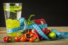 Bicchieri d'acqua e un metro del ` s del sarto Frutta e verdure Il concetto di perdita di peso Dieta sana Immagine Stock