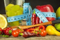 Bicchieri d'acqua e un metro del ` s del sarto Frutta e verdure Il concetto di perdita di peso Dieta sana Fotografia Stock