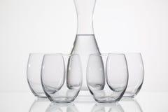 Bicchieri d'acqua sulla tavola di vetro Fotografie Stock