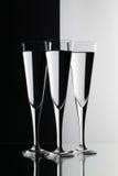 Bicchieri d'acqua sullo scrittorio di vetro Immagini Stock