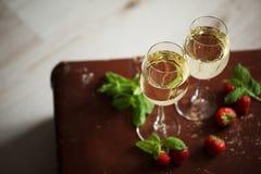 Bicchieri di vino con vino bianco decorato con la fragola e la menta Fotografia Stock