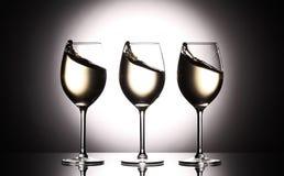 Bicchieri di vino con vino bianco - liquido transperent - sul fondo dello studio Immagini Stock