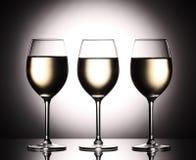 Bicchieri di vino con vino bianco - liquido transperent - sul fondo dello studio Fotografie Stock Libere da Diritti
