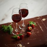 Bicchieri di vino con vino rosso decorato con la fragola e la menta Immagini Stock Libere da Diritti