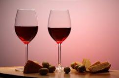 Bicchieri di vino con vino rosso su legno con formaggio ed olive verdi Fondo dello studio Fotografie Stock