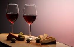 Bicchieri di vino con vino rosso su legno con formaggio ed olive verdi Fondo dello studio Fotografia Stock