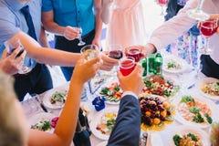 Bicchieri di vino del tintinnio della gente al partito di festa Immagini Stock