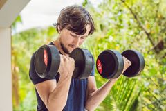 Bicep curl - weight training fitness man outside working out arm. S lifting dumbbells doing biceps curls. Male sports model exercising outdoors as part of Royalty Free Stock Photos