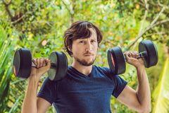Bicep curl - weight training fitness man outside working out arms lifting dumbbells doing biceps curls. Male sports. Model exercising outdoors as part of Royalty Free Stock Photography