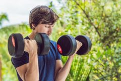 Bicep curl - weight training fitness man outside working out arms lifting dumbbells doing biceps curls. Male sports. Model exercising outdoors as part of royalty free stock photos