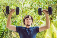 Bicep curl - weight training fitness man outside working out arms lifting dumbbells doing biceps curls. Male sports. Model exercising outdoors as part of royalty free stock image