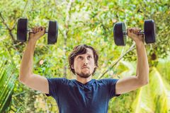 Bicep curl - weight training fitness man outside working out arms lifting dumbbells doing biceps curls. Male sports model exercisi stock image