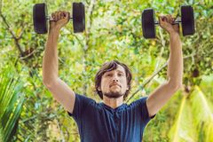 Bicep curl - weight training fitness man outside working out arms lifting dumbbells doing biceps curls. Male sports model exercisi. Ng outdoors as part of Royalty Free Stock Photos