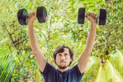 Bicep curl - weight training fitness man outside working out arm. S lifting dumbbells doing biceps curls. Male sports model exercising outdoors as part of Royalty Free Stock Photo