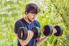 Bicep curl - weight training fitness man outside working out arm. S lifting dumbbells doing biceps curls. Male sports model exercising outdoors as part of Stock Photography