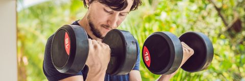 Bicep curl - weight training fitness man outside working out arms lifting dumbbells doing biceps curls. Male sports model exercisi. Ng outdoors as part of royalty free stock photo
