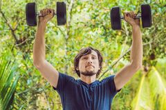Bicep curl - weight training fitness man outside working out arms lifting dumbbells doing biceps curls. Male sports. Model exercising outdoors as part of royalty free stock images