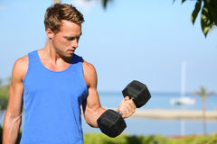 Bicep curl - weight training fitness man outside. Working out arms lifting dumbbells doing biceps curls. Male sports model exercising outdoors as part of Stock Photo