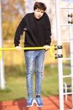 Bicepens för arm för tonåringpojkeutbildning drar upp i utomhus- idrottshall i stad parkerar slut upp fotoet arkivbild