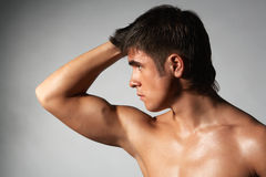 Biceps. Close-up portrait of young naked muscular athlete; isolated on gray Royalty Free Stock Image