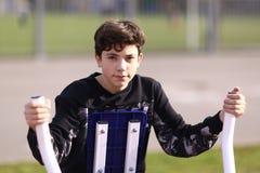 Biceps de bras de formation de garçon d'adolescent dans le gymnase extérieur dans la fin de parc de ville vers le haut de la phot photos stock