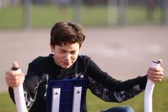 Biceps de bras de formation de garçon d'adolescent dans le gymnase extérieur dans la fin de parc de ville vers le haut de la phot photographie stock libre de droits