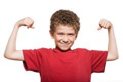 Biceps de fléchissement intense de muscle de verticale de petit garçon image stock