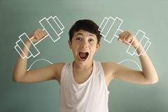 Biceps de l'adolescence d'exposition de garçon avec les cloches muettes dessinées avec la photo drôle de craie Photos libres de droits