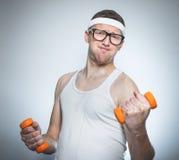 Biceps de levage d'homme faible drôle Photo stock