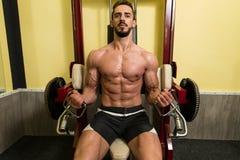 Biceps Exercises On A Machine Stock Photo