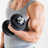Biceps. Young muscular man lifting the weights with biceps exercise. Close-up royalty free stock photo