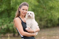 Bichon bolognese dog with beautiful woman in the park. Bichon bolognese dog with beautiful owner in the park stock image