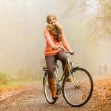 Bici activa feliz del montar a caballo de la mujer en parque del otoño Foto de archivo