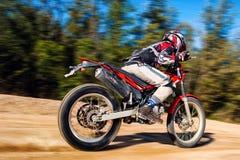 Bici adolescente del motocrós del montar a caballo del muchacho en el camino de la grava Imagen de archivo libre de regalías