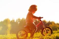 Bici al tramonto, bambini attivi di guida della bambina Fotografia Stock