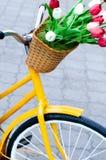Bici amarilla con una cesta en la cual un ramo de tulipanes fotografía de archivo libre de regalías