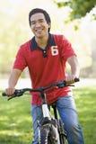 Bici asiática del montar a caballo del hombre en parque Fotos de archivo