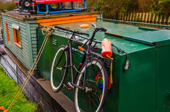 Bici atada con correa a los barcos coloreados viejos en el canal Imágenes de archivo libres de regalías