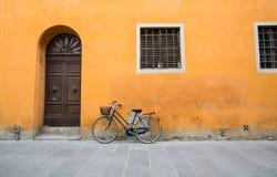 Bici azul con la cadena amarilla en la pared anaranjada Imagen de archivo