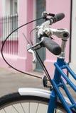 Bici azul y casa rosada Fotos de archivo libres de regalías
