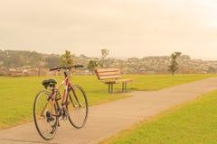Bici, banco y la visión desde la colina, Whangaparaoa, alrededor de Auckland, Nueva Zelanda Foto de archivo libre de regalías