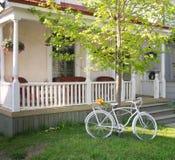 Bici blanca decorativa en frente de la casa. Imagen de archivo libre de regalías