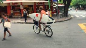 Bici brasileña del montar a caballo del hombre de Carioca con la tabla hawaiana Río almacen de video