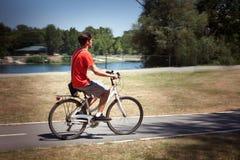Bici casual del paseo del hombre joven por el día de verano del lago imagen de archivo