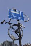 Bici che appende fuori da un segnale stradale Fotografie Stock Libere da Diritti